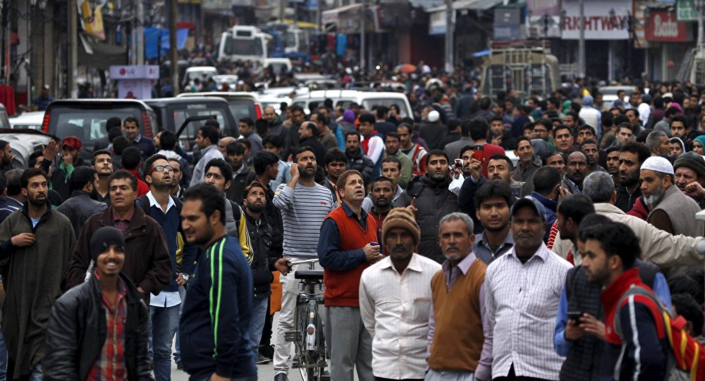 People stand on a road after vacating buildings following an earthquake in Srinagar