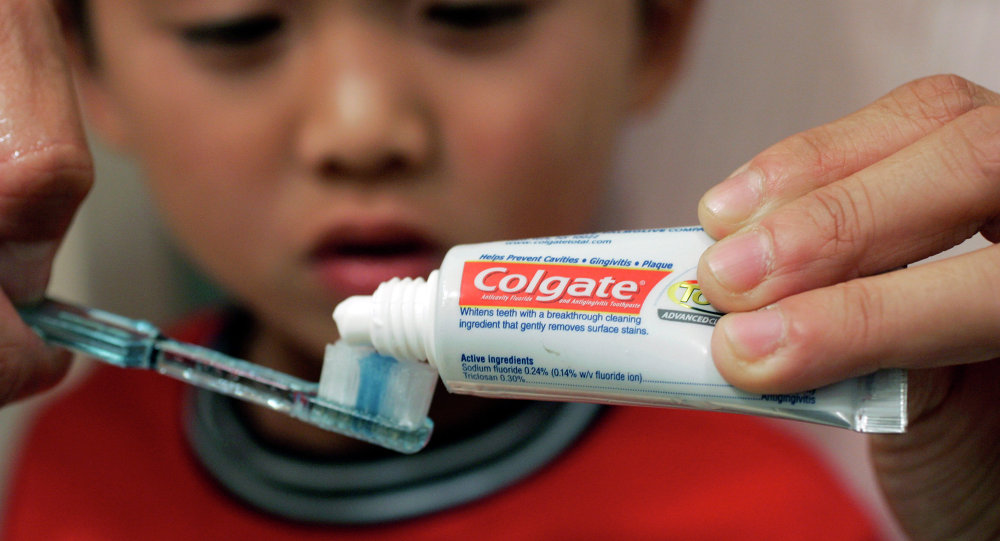 Yvonne Chu puts Colgate toothpaste on a tooth brush for her son, Skyler Fong, 6, in Palo Alto, Calif.