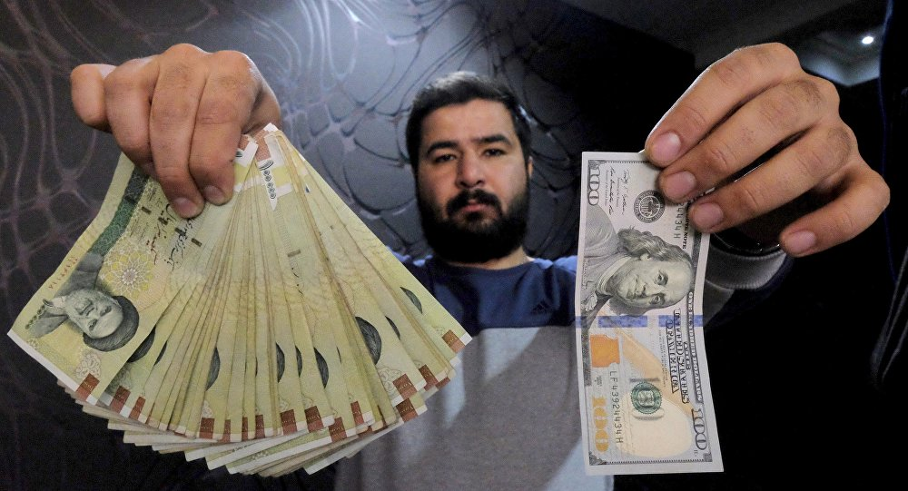 A سقوط قیمت ارز، شبی سیاه برای دلالانchanger poses for the camera with a US dollar (R) and the amount being given when converting it into Iranian rials (L), at a currency exchange shop in Tehran's business district, Iran, in this January 20, 2016 file photo