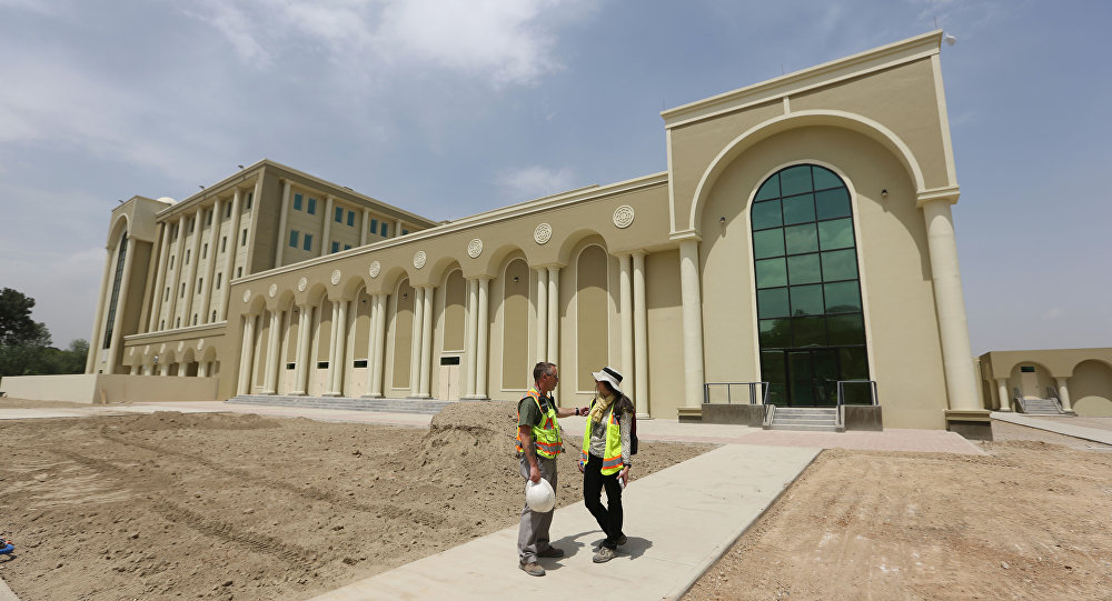 In this Wednesday, May 6, 2015, photo, U.S. engineers chat in front of Afghanistan's new Defense Ministry building, in Kabul, Afghanistan