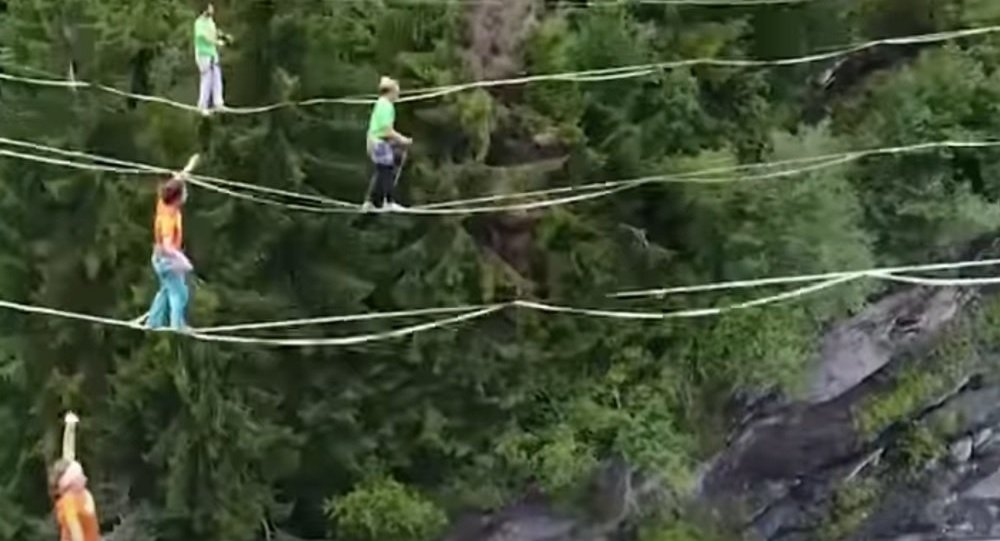 Athletes Perform Tricks On Ropes Above An Abyss