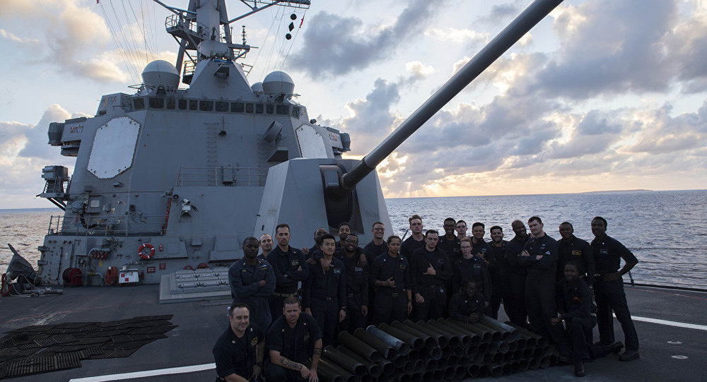 Sailors pose for a group photo on the forcastle after participating in a Naval Surface Fire Support (NSFS) aboard the forward-deployed Arleigh Burke-class guided-missile destroyer USS Mustin (DDG 89). Mustin is operating as part of the Ronald Reagan Strike Group in the U.S. 7th Fleet area of operations, a combat-ready force that protects and defends the collective maritime interest of it's allies and partners in the Indo-Asia-Pacific.